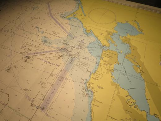 Planning for San Francisco. The chart of the harbour and Golden Gate Bridge. All happening on the navigation table on The Bridge.